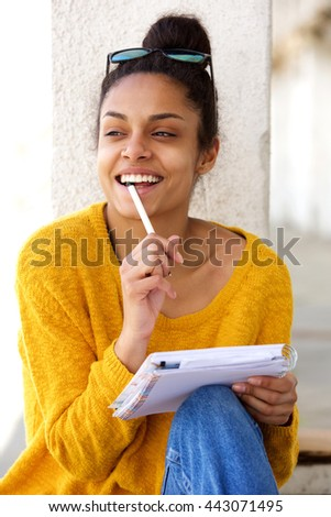 Close up portrait of young african female sitting outside thinking and writing book - stock photo