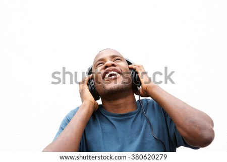 Close up portrait of young african guy enjoying music on headphones against white background  - stock photo