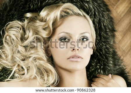 close up portrait of young alluring beautiful girl with blond curly hair wearing a black bra with fur around her - stock photo