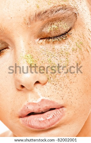 Close-up portrait of young alluring woman with eyes closed and with powder on her face. - stock photo
