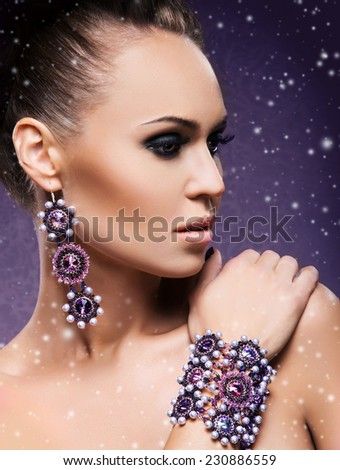 Close-up portrait of young and beautiful lady in a precious earrings and a bracelet on her hand. Winter background with a snow. - stock photo