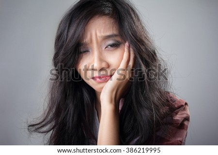 Close up portrait of young Asian woman expressing pain of having a toothache, over grey background - stock photo