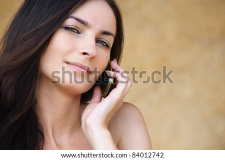 Close-up portrait of young attractive brunette woman speaking on mobile phone against yellow background. - stock photo