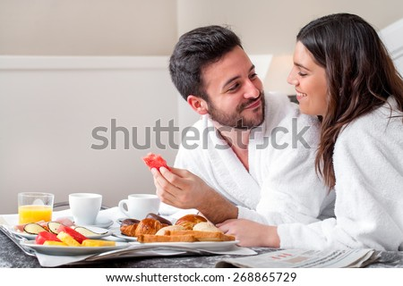 Close up portrait of young attractive couple enjoying breakfast in hotel room. - stock photo