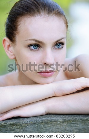 Close-up portrait of young attractive dark-haired woman at summer green park. - stock photo
