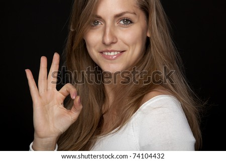Close-up portrait of young attractive female showing OK sign isolated on black - stock photo