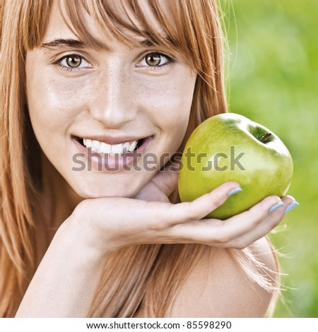 Close-up portrait of young attractive woman holding an apple, propping up her face and smiling at summer green park. - stock photo