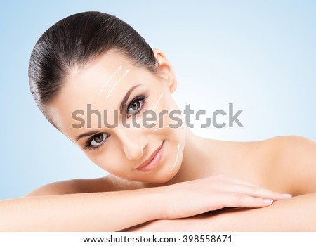 Close-up portrait of young, beautiful and healthy woman ready for plastic surgery treatment (collage with arrows) - stock photo