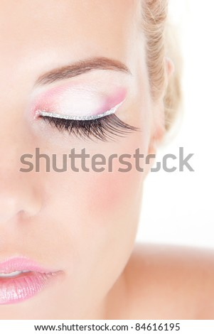 Close-up portrait of young beautiful blond girl with closed eyes and pink make-up - stock photo