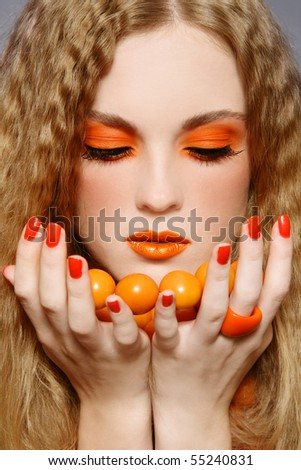 Close-up portrait of young beautiful blond girl with fancy makeup and orange necklace - stock photo