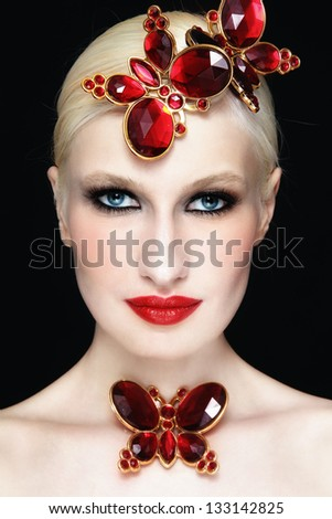 Close-up portrait of young beautiful blond girl with stylish make-up and red plastic butterflies - stock photo