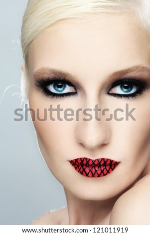 Close-up portrait of young beautiful blond woman with fancy make-up - stock photo