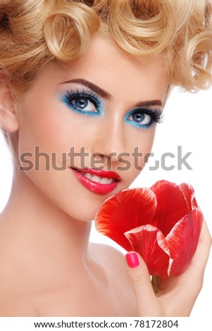 Close-up portrait of young beautiful blond woman with fancy make-up and red flower in hand, on white background - stock photo