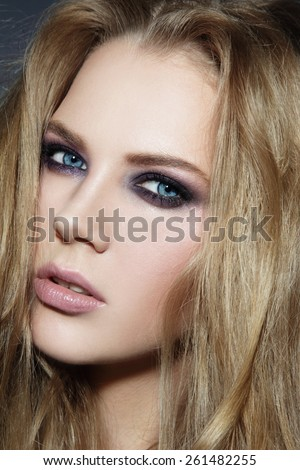 Close-up portrait of young beautiful blonde woman with smoky eyes make-up - stock photo