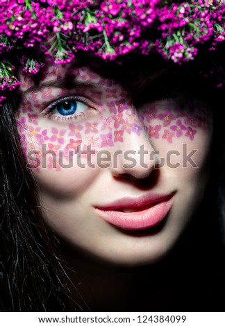 Close-up portrait of young beautiful blue-eyed woman with flowered wreath and creative make up - stock photo