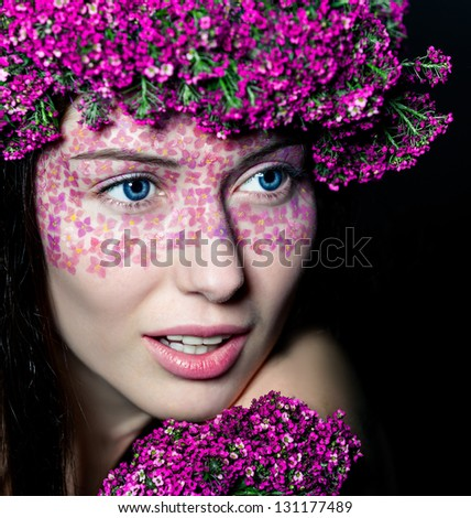 Close-up portrait of young beautiful blue-eyed woman with flowered wreath and fashionable makeup