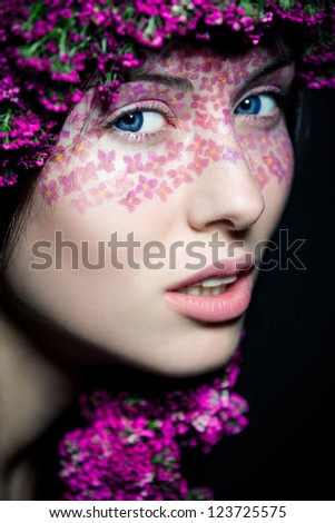 Close-up portrait of young beautiful blue-eyed woman with flowered wreath and stylish makeup