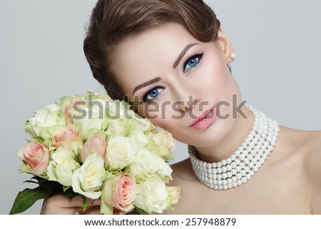 Close-up portrait of young beautiful bride with stylish make-up and hairdo holding bouquet  - stock photo