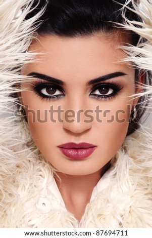 Close-up portrait of young beautiful brunette with stylish make-up with white fur around - stock photo