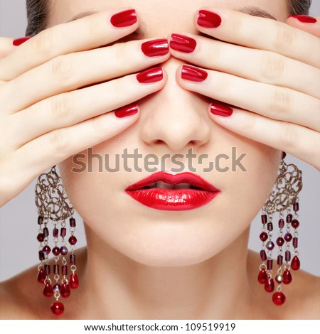 close-up portrait of young beautiful brunette woman in ear-rings closing her eyes with manicured hands - stock photo