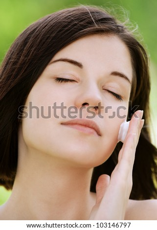Close-up portrait of young beautiful brunette woman putting white cream on her face at summer green park
