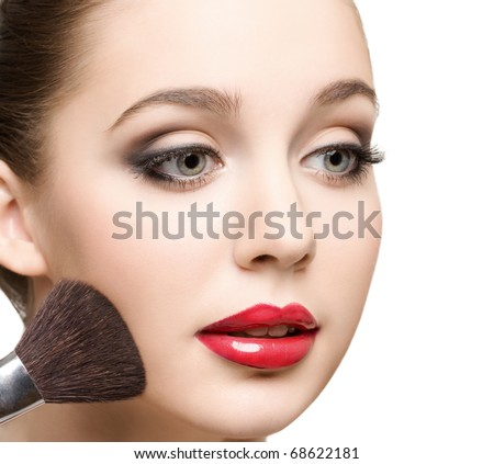 close-up portrait of young beautiful caucasian woman applying  powder to her cheeks