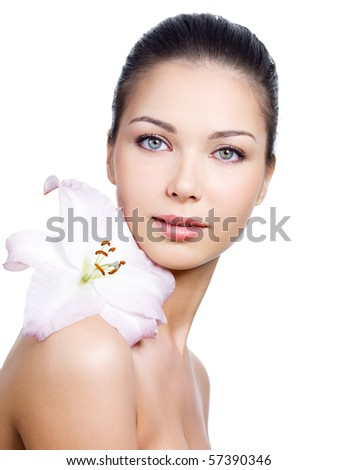 Close-up portrait of young beautiful face of woman with clean skin and flower on a shoulder - white background
