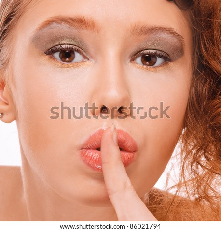Close-up portrait of young beautiful fair-haired woman holding her finger near lips against white background. - stock photo