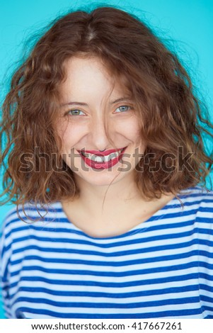 Close up portrait of young beautiful girl smiling to camera. Hipster young woman with natural makeup and curly hair on blue background, not isolated. - stock photo