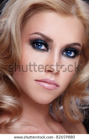 Close-up portrait of young beautiful girl with blond curly hair and stylish sparkly make-up - stock photo
