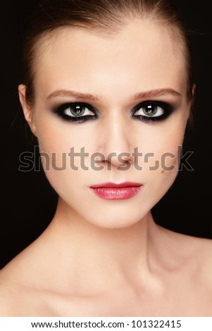 Close-up portrait of young beautiful girl with smoky eyes