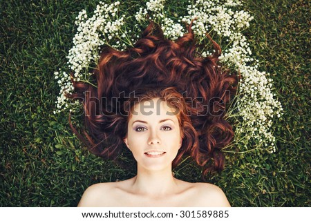 Close up portrait of young beautiful girl woman with red brown hair laying on grass with white small flowers around her head .View from above top overhead. Concept of spring summer youth happiness - stock photo