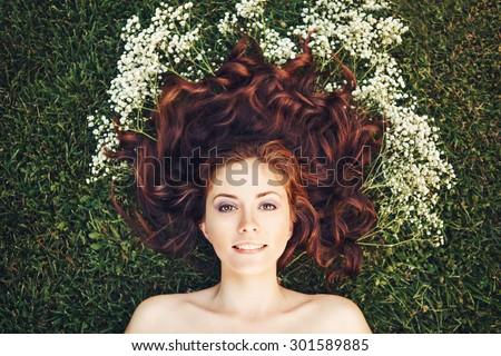 Đóng lên chân dung của trẻ phụ nữ cô gái xinh đẹp với mái tóc màu nâu đỏ nằm trên cỏ với hoa nhỏ màu trắng quanh đầu từ trên đầu overhead .view.  Khái niệm của mùa xuân hè trẻ hạnh phúc