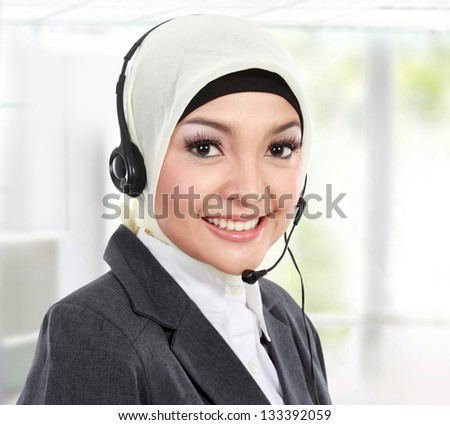 close up portrait of Young beautiful Muslim woman customer service operator with headset on white background - stock photo