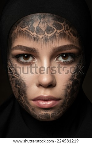 Close-up portrait of young beautiful nun with faceart over dark background - stock photo