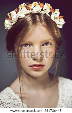 Close up portrait of young beautiful pretty cute teenage girl. Emotive portrait of a beautiful teen girl with healthy glossy hair and flowers on her head. Close up. Studio shot - stock photo