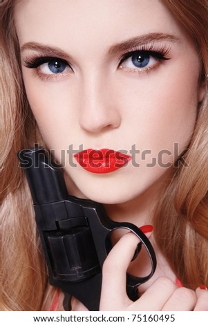 Close-up portrait of young beautiful sexy blond woman with revolver in hand - stock photo