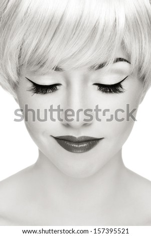 Close-up portrait of young beautiful smiling blond woman with cat eyes make-up - stock photo