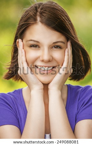 Close-up portrait of young beautiful smiling woman propping up her face in front of summer green park. - stock photo