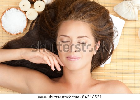 Close-up portrait of young beautiful spa woman with long brown hair lying on bamboo mat at spa salon - stock photo