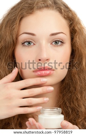 Close-up portrait of young beautiful woman applying moisturizing cream on her face, isolated on white background - stock photo