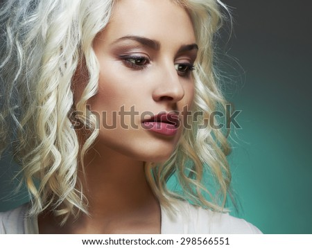 close-up portrait of young beautiful woman.Blond girl. Curly hairstyle.green background - stock photo