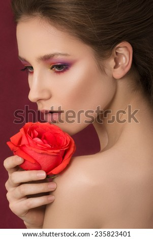 Close-up portrait of young beautiful woman holding red rose. Spa concept. - stock photo