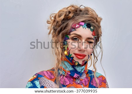 Close up portrait of young beautiful woman, model,  clown. Bright creative fantasy makeup, geometric shapes, circles. Multicolored paint, red, blue, orange, yellow, pink. Pop art style, avant garde. - stock photo