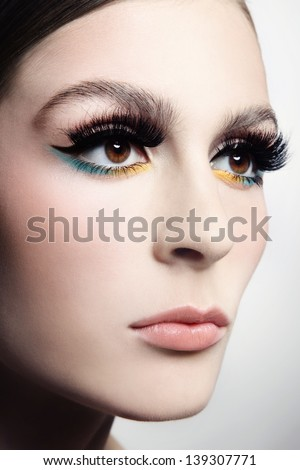 Close-up portrait of young beautiful woman with cat eye make-up and fancy false eyelashes - stock photo