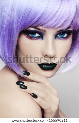 Close-up portrait of young beautiful woman with colorful fancy make-up and violet wig - stock photo