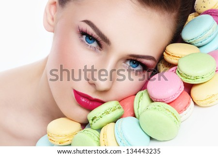 Close-up portrait of young beautiful woman with colorful macaroons - stock photo