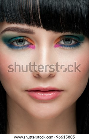 Close-up portrait of young beautiful woman with colorful stylish make-up - stock photo