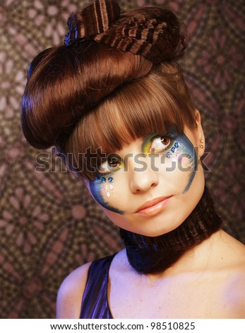 Close-up portrait of young beautiful woman with colorful stylish make-up