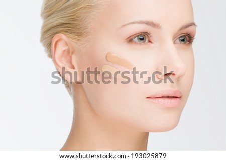 close-up portrait of young beautiful woman with cosmetic foundation - stock photo